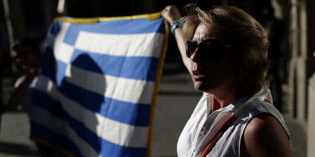 People protest during a pro Greece demonstration at the European Union Office in Barcelona, Spain, Monday, June 29, 2015. Spain's economy minister has said a Greek debt deal is still reachable, although Spain's benchmark Ibex stock index slid nearly 4 percent Monday morning. (AP Photo/Manu Fernandez)