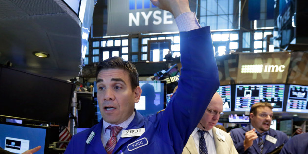 Specialist Robert Tuccillo, left, works at his post on the floor of the New York Stock Exchange, Tuesday, June 30, 2015.  U.S. stocks are rising broadly in early trading as investors hope for a last-minute deal on Greece's debt woes. (AP Photo/Richard Drew)