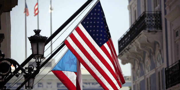 The U.S. and Puerto Rico flags wave in front of the governor's mansion in Old San Juan, Puerto Rico, Monday, June 29, 2015. International economists released a critical report on Puerto Rico's economy Monday on the heels of the governor's warning that the island can't pay its $72 billion public debt. (AP Photo/Ricardo Arduengo)