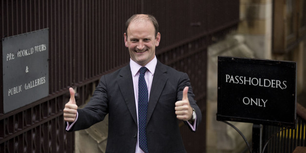 Newly elected U.K. Independence Party (UKIP) Member of Parliament Douglas Carswell gives a double thumbs-up as he poses for the media upon his arrival to take his seat at the Houses of Parliament in London, Monday, Oct. 13, 2014. The U.K. Independence Party won a seat in the British Parliament for the first time on Friday, a significant breakthrough for the anti-immigration force and a protest vote against the country's mainstream parties. UKIP candidate Douglas Carswell won the special election in the eastern England constituency of Clacton-on-Sea with 21,113 votes. (AP Photo/Matt Dunham)
