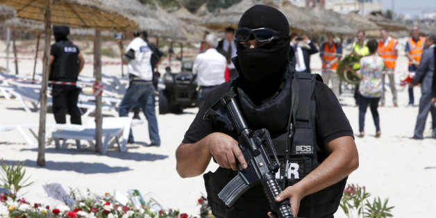 A hooded Tunisian police officer stands guard ahead of the visit of top security officials of Britain, France, Germany and Belgium at the scene of Friday's shooting attack in front of the Imperial Marhaba hotel in the Mediterranean resort of Sousse, Tunisa, Monday, June 29, 2015. The top security officials of Britain, France, Germany and Belgium are paying homage to the people killed in the terrorist attack on Friday. (AP Photo/Abdeljalil Bounhar)