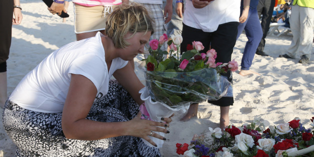 An unidentified tourist places flowers at the scene of Friday's shooting attack in the coastal town of Sousse, Tunisia, Sunday, June 28, 2015. The Friday attack on tourists at a beach is expected to be a huge blow to Tunisia's tourism sector, which made up nearly 15 percent of the country's gross domestic product in 2014. (AP Photo/Abdeljalil Bounhar)