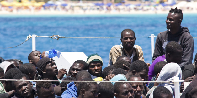 Migrants wait to disembark from a Coast Guard ship that rescued them at sea, in the Island of Lampedusa, Italy, Tuesday, June 23, 2015. In the past months, thousands of migrants have been crossing the Mediterranean to reach Italy and Greece. Some 2,000 are missing and feared dead. (AP Photo/Mauro Seminara)