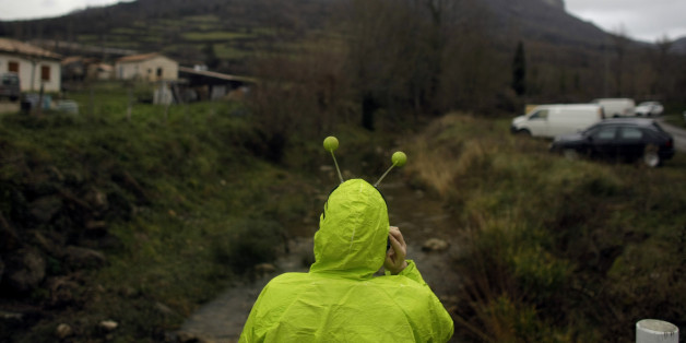 A woman dressed in an alien costume attends a small party in the town of Bugarach, France, Friday, Dec. 21, 2012. Although the long expected end of the Mayan calendar has come, the New Age enthusiasts have steered clear from the sleepy French town of Bugarach, which gave some locals a chance to joke about the UFO legends that surround the area. (AP Photo/Marko Drobnjakovic)