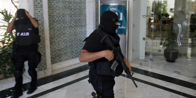 Tunisian police officers guard the Imperial Marhaba hotel during visit of top security officials of Britain, France, Germany and Belgium in Sousse, Tunisia, Monday, June 29, 2015. British Home Secretary Theresa May, French Interior Minister Bernard Cazeneuve, German Interior Minister Thomas de Maiziere and Belgian Interior Minister Jan Jambon joined their Tunisian counterpart on the beach in front of the Imperial Marhaba hotel in the Mediterranean resort of Sousse for a tribute to the dead and wounded on Monday. (AP Photo/Darko Vojinovic)