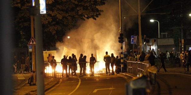 Protesters clash with riot police forces in The Hague's Schilderswijk district, the Netherlands, late June 29, 2015, after Mitch Henriquez from Aruba died in police custody on June 28. Henriquez was arrested on June 27 at the Night at the Park festival in The Hague after saying that he had a weapon.   AFP PHOTO / ANP / ARIE KIEVIT   -- The Netherlands out --        (Photo credit should read ARIE KIEVIT/AFP/Getty Images)