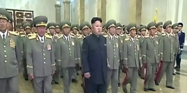 In this Tuesday, July 8, 2014 image made from video, North Korean leader Kim Jong Un, center, visits Kumsusan Palace of the Sun to mark the 20th anniversary of the death of its first leader, Kim Il Sung, in Pyongyang, North Korea. Kim seemed to have somehow hurt his leg enough to require a slight, but visible, limp as he marched across the stage Tuesday to assume his position of honor. He limped again as he left the room when the event was over. (AP Photo/KRT via AP Video) TV OUT, NORTH KOREA OU