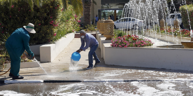Workers clean a sidewalk in the garden of the Imperial Marhaba hotel where a shooting attack took place Friday in Sousse, Tunisia, Saturday, June 27, 2015. The morning after a lone gunman killed dozens of people at a beach resort in Tunisia, busloads of tourists are heading to the nearby Enfidha-Hammamet airport hoping to return to their home countries. (AP Photo/Darko Vojinovic)