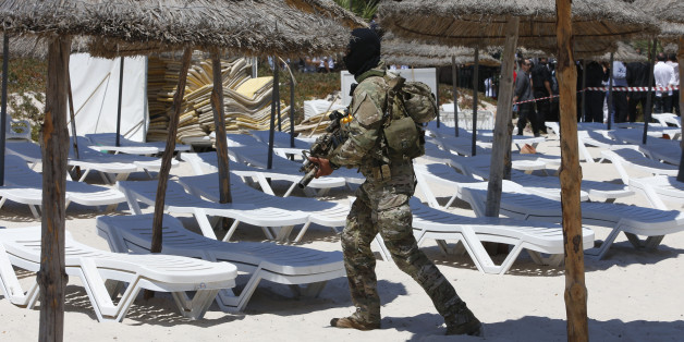 A hooded Tunisian police officer patrols  ahead of the visit of top security officials of Britain, France, Germany and Belgium at the scene of Friday's shooting attack in front of the Imperial Marhaba hotel in the Mediterranean resort of Sousse, Tunisa, Monday, June 29, 2015. The top security officials of Britain, France, Germany and Belgium are paying homage to the people killed in the terrorist attack on Friday. (AP Photo/Abdeljalil Bounhar)