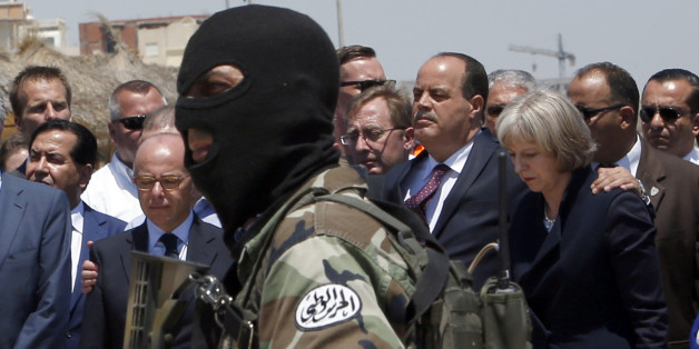 A hooded Tunisian police officer stands guard as British Home Secretary Theresa May, right, Tunisian Interior Minister Mohamed Najem Gharsalli, 2nd right, and French Interior Minister Bernard Cazeneuve, left, pay respect to the victims of Friday's shooting attack on the beach in front of the Imperial Marhaba hotel in the Mediterranean resort of Sousse, Tunisa, Monday, June 29, 2015. Seven people are being interrogated in Tunisia's capital in the investigation into a deadly beach resort attack th