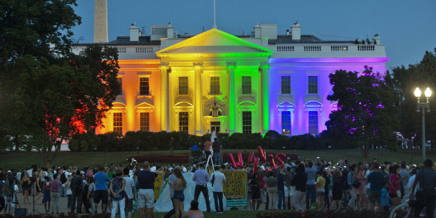 FILE - In this Friday, June 26, 2015 file photo, people gather in Lafayette Park to see the White House illuminated with rainbow colors in commemoration of the Supreme Court's ruling to legalize same-sex marriage in Washington. (AP Photo/Pablo Martinez Monsivais)
