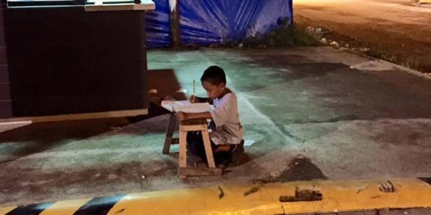 Kleiner Junge lernt nachts im Licht der Straßenlaternen um einem Arzt zu werden