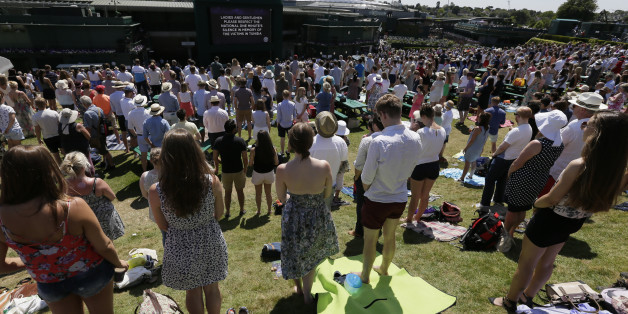 People observe the minute silence for the victims of the shooting in Tunisia last week, at the All England Lawn Tennis Championships in Wimbledon, London, Friday July 3, 2015. Fans and staff at Wimbledon observed a minute's silence for the victims of last Friday's attack in Tunisia, in which 30 Britons were killed in a shooting rampage at a beach resort in Sousse.  The start of play at Wimbledon was delayed so the tournament could join in the national minute's silence. (AP Photo/Tim Ireland)