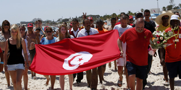 Tourists and residents, some displaying a Tunisian flag, walk on the beach to the scene of the attack in Sousse, Tunisia, Sunday, June 28, 2015. The Friday attack on tourists at a beach is expected to be a huge blow to Tunisia's tourism sector, which made up nearly 15 percent of the country's gross domestic product in 2014. (AP Photo/Abdeljalil Bounhar)