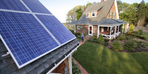 "FILE - In this May 8, 2009 file photo, Len Bicknell walks from his house to his garage where his solar energy panels are mounted on the roof in Marshfield, Mass. The increasing popularity of home solar panels is prompting environmental groups in Massachusetts to press state lawmakers to lift what they say are the state's arbitrary solar energy ""net-metering caps."" (AP Photo/Stephan Savoia, File)"