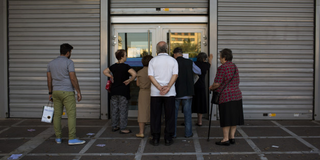 People wait to be allowed into a bank to withdraw a maximum of 120 euros ($134) for the week, in central Athens, Friday, July 3, 2015. As Greek banks and markets remain closed Friday for a fifth day, rival campaigns scrambled to roll out their messages. And a prediction from the International Monetary Fund that Greece will need piles of additional cash from eurozone countries and others over the next three years put even more pressure on the government. (AP Photo/Emilio Morenatti)