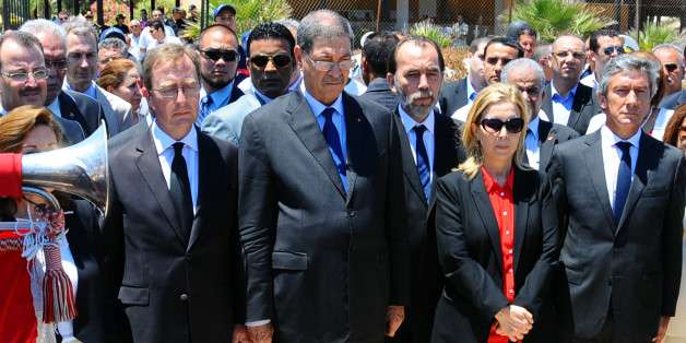 Tunisian Prime Minister Habib Essid, 2nd left, observes a one minute's silence near the Imperial Marhaba hotel in the Mediterranean resort town of Sousse, to honor the victims of a deadly beach attack a week ago that killed 38 people, Friday, July 3, 2015. Eight people are in custody in Tunisia, suspected of having direct links to a deadly beach attack that killed 38 people, but four other possible suspects have been released, a minister said Thursday. (AP Photo/Hassene Dridi)