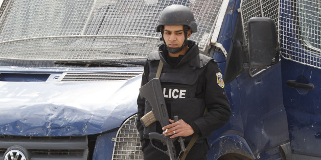 An armed Tunisian police officer, stands guard at the morgue of the Charles Nicolle hospital in Tunis, Tunisia, Friday, March 20, 2015. The two extremist gunmen who killed 21 people at a museum in Tunis trained in neighboring Libya before caring out the deadly attack, a top Tunisian security official said. (AP Photo/Michel Euler)