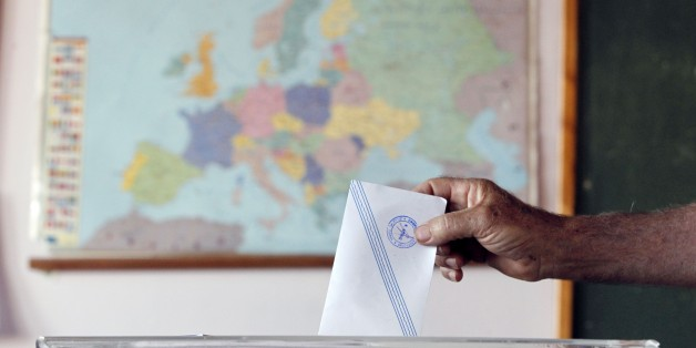 A man casts his vote as the map of Europe is seen in the background at a polling station in Athens, Sunday, July 5, 2015. Greeks began voting early Sunday in a closely-watched, closely-contested referendum, which the government pits as a choice over whether to defy the country's creditors and push for better repayment terms or essentially accept their terms, but which the opposition and many of the creditors paint as a choice between staying in the euro or leaving it. (AP Photo/Thanassis Stavrak