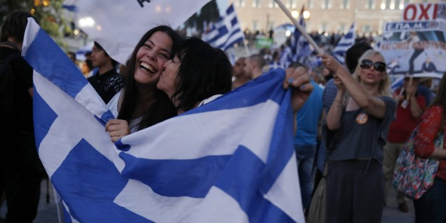 Supporters of the No vote react after the first results of the referendum at Syntagma square in Athens, Sunday, July 5, 2015. Greece faced an uncharted future as its interior ministry predicted Sunday that more than 60 percent of voters in a hastily called referendum had rejected creditors' demands for more austerity in exchange for rescue loans. (AP Photo/Petros Giannakouris)