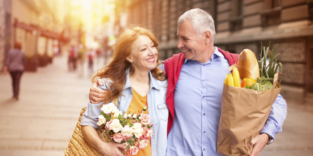 Mature couple outdoors on street with grocery bags.