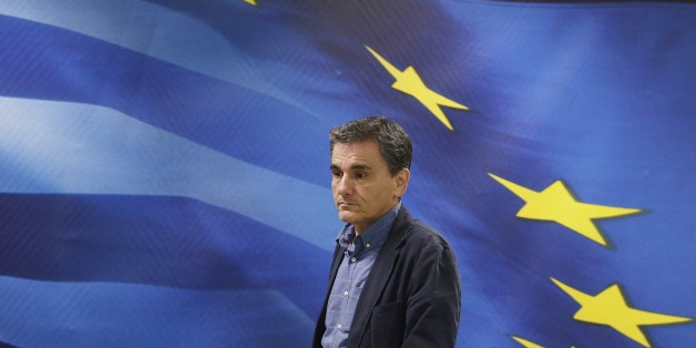 New Greek Finance Minister Euclid Tsakalotos arrives for a hand over ceremony in Athens, Monday, July 6, 2015. Following Sunday's referendum the Greece and its membership in Europe's joint currency faced an uncertain future Monday, with the country under pressure to restart bailout talks with creditors as soon as possible after Greeks resoundingly rejected the notion of more austerity in exchange for aid. (AP Photo/Petr David Josek)