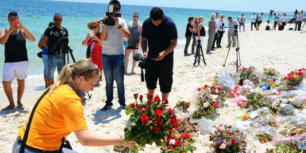 An unidentified tourist lays flowers to honor the victims of a deadly beach attack a week ago that killed 38 people, near the Imperial Marhaba hotel in the Mediterranean resort town of Sousse, Friday, July 3, 2015. Eight people are in custody in Tunisia, suspected of having direct links to a deadly beach attack that killed 38 people, but four other possible suspects have been released, a minister said Thursday. (AP Photo/Hassene Dridi)