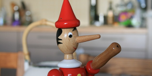 Wooden Pinocchio on the table. Pinocchio is known for having a long nose that becomes longer when he is under stress, especially while telling a lie.
