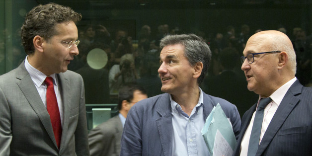 Greek Finance Minister Euclid Tsakalotos, center, speaks with Dutch Finance Minister Jeroen Dijsselbloem, left, and French Finance Minister Michel Sapin during a round table meeting of eurozone finance ministers at the EU LEX building in Brussels on Tuesday, July 7, 2015. Greek Prime Minister Alexis Tsipras was heading Tuesday to Brussels for an emergency meeting of eurozone leaders, where he will try to use a resounding referendum victory to eke out concessions from European creditors over a ba