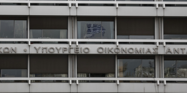 A Greek flag is reflected on a glass window of the Finance Ministry in Athens, Monday, Feb. 23, 2015. Greece will present a list of proposed reforms to debt inspectors on Monday to get final approval for an extension to its rescue loans. But already the government was facing dissent within its ruling party over claims it is backtracking on its promise to ease budget cuts for the recession-battered Greeks. (AP Photo/Yorgos Karahalis)
