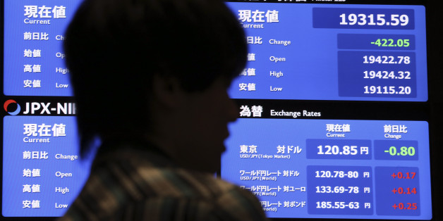 A local media reports the day's loss of Japan's Nikkei stock index in front of an electronic board at Tokyo Stock Exchange in Tokyo Thursday, July 9, 2015. Asian stocks markets were volatile on Thursday as China's main index seesawed after a prolonged sell-off while Hong Kong's benchmark rebounded strongly. (AP Photo/ Eugene Hoshiko)