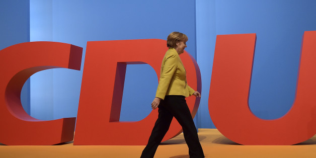 Chancellor and chairwoman of the German Christian Democrats, CDU, Angela Merkel, walks in front of a party logo during the 27th party convention in Cologne, Germany, Wednesday, Dec. 10, 2014. (AP Photo/Martin Meissner)