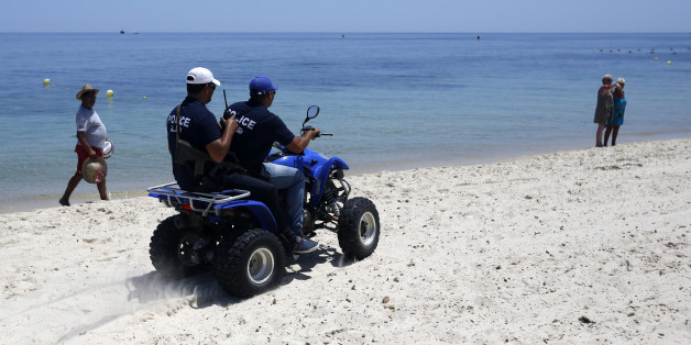 Tunisian police officers patrol on a beach in front of the Imperial Marhaba Hotel in Sousse, Tunisia, Sunday, June 28, 2015. Tunisia's top security official says 1,000 extra police are being deployed at tourist sites and beaches in the North African nation. (AP Photo/Darko Vojinovic)