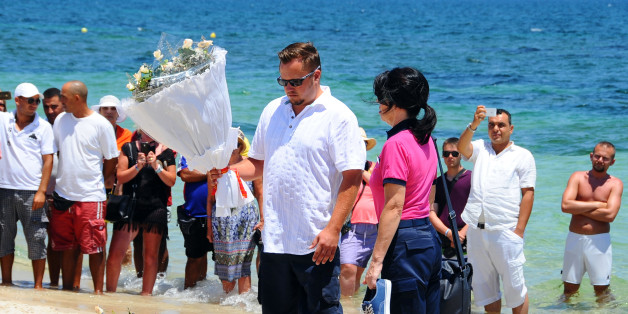 Unidentified tourists lay flowers to honor the victims of a deadly beach attack a week ago that killed 38 people, near the Imperial Marhaba hotel in the Mediterranean resort town of Sousse, Friday, July 3, 2015. Eight people are in custody in Tunisia, suspected of having direct links to a deadly beach attack that killed 38 people, but four other possible suspects have been released, a minister said Thursday. (AP Photo/Hassene Dridi)