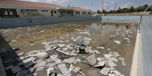 In this Tuesday, Aug. 5, 2014 photo, murky water and rubbish fill an abandoned training pool for athletes at the Olympic village in northern Athens. The latest government estimate sets the final cost of the Games at 8.5 billion euros, double the original budget but a drop in the ocean of the country's subsequent 320 billion-euro debt, which spun out of control after 2008. (AP Photo/Thanassis Stavrakis)