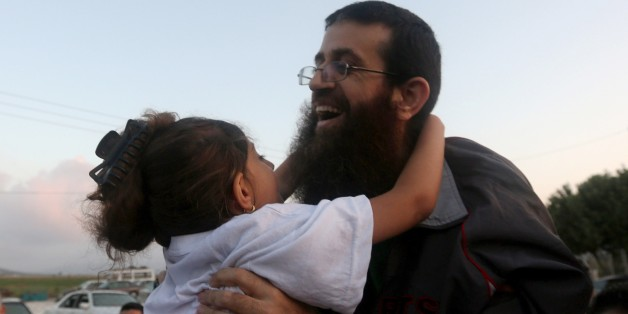 Khader Adnan, a Palestinian prisoner who staged a 56-day hunger strike while being detained for a year without charge by Israeli authorities, hugs a relative as he arrives in the West Bank village of Arraba after his release early on July 12, 2015. Adnan, 37, was detained a year ago, shortly after the kidnapping and murder of three young Israelis, which triggered the arrests of hundreds of Palestinians in the occupied West Bank. AFP PHOTO /JAAFAR ASHTIYEH        (Photo credit should read JAAFAR