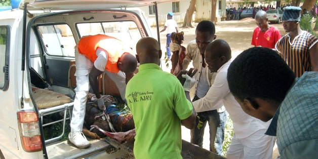 **GRAPHIC CONTENT** Health officials carry the body of a victim  of a suicide bomb attack out of an ambulance in  Potiskum, in northeast Nigeria's Yobe State, on June 15, 2015. Ten people were killed in twin suicide bombings in Potiskum, northeast Nigeria, a police source and a civilian vigilante assisting the military against Boko Haram told AFP on June 15. Eight vigilantes were killed in the first blast in the Igwanda area of the city, while two died in the second outside a tavern and brothel in the Dorawa area. AFP PHOTO / AMINU ABUBAKAR        (Photo credit should read AMINU ABUBAKAR/AFP/Getty Images)