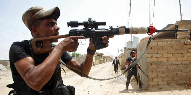 Iraqi Shiite fighters from the Popular Mobilisation force keep position during a battle against jihadists from the Islamic State group to retake the strategic town Baiji, north of Tikrit, on June 8, 2015.  Baghdad regained control of Baiji -- located on the road to IS hub Mosul and near the country's largest oil refinery -- last year, but subsequently lost it again.  AFP PHOTO / AHMAD AL-RUBAYE        (Photo credit should read AHMAD AL-RUBAYE/AFP/Getty Images)