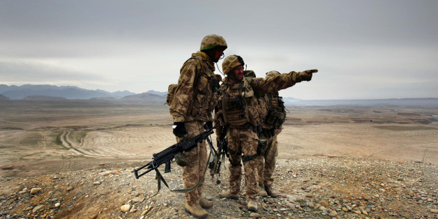 A soldier of 42 Commandos of British Royal Marines points at a location of Taliban militants during an operation near Kajaki, southern Afghanistan, Saturday, Jan. 13, 2007.