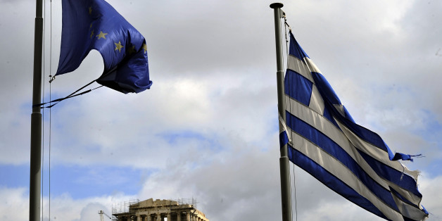 Ripped EU and Greek flags flutter in Athens on February 9, 2012.   The debt rescue for Greece hits an 11th-hour hurdle on pension cuts, with eurozone ministers poised to meet on a package to avert default and Greek unions calling another general strike to fight the terms. AFP PHOTO/ LOUISA GOULIAMAKI        (Photo credit should read LOUISA GOULIAMAKI/AFP/Getty Images)