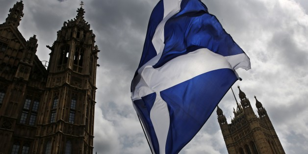 A member of public flies a giant Scottish Saltire flag outside the Houses of Parliament