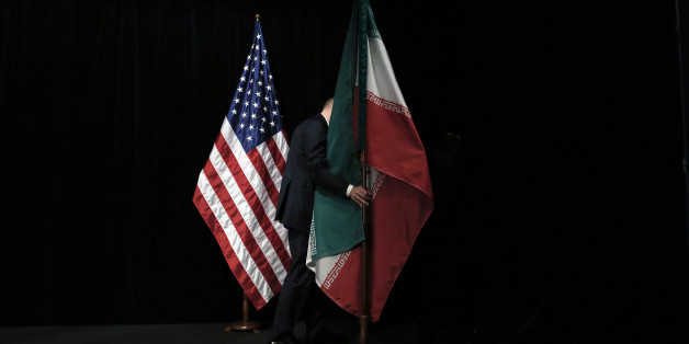 A staff member removes the Iranian flag from the stage after a group picture with foreign ministers and representatives of Unites States, Iran, China, Russia, Britain, Germany, France and the European Union during the Iran nuclear talks at the Vienna International Center in Vienna, Austria Tuesday July 14, 2015.  After 18 days of intense and often fractious negotiation, world powers and Iran struck a landmark deal Tuesday to curb Iran's nuclear program in exchange for billions of dollars in reli