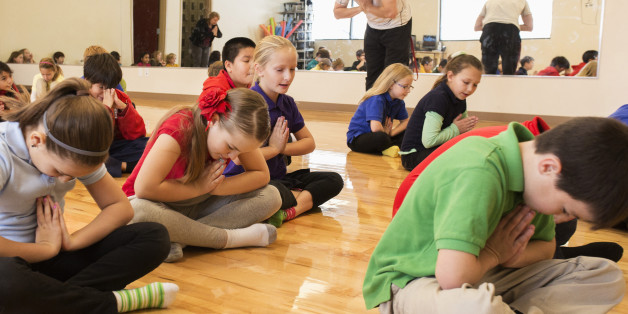 Children meditating in gym class