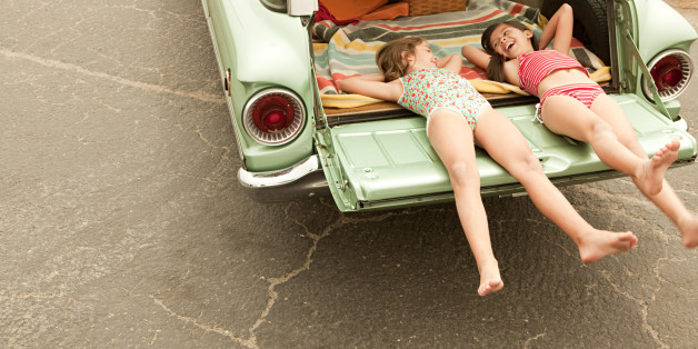 Two girls lying in estate car