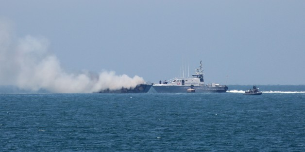 A picture shows an Egyptian naval vessel approaching another army boat on fire on the maritime border between Egypt and the Palestinian Gaza Strip, off the coast of Rafah in southern Gaza, on July 16, 2015. The Egyptian army said the vessel was set ablaze during a clash with militants in the restive Sinai Peninsula. AFP PHOTO / SAID KHATIB        (Photo credit should read SAID KHATIB/AFP/Getty Images)