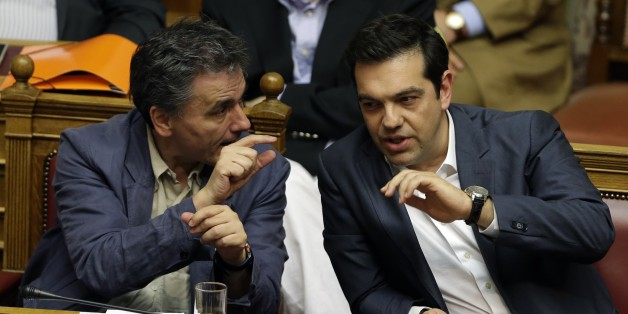 Greece's Prime Minister Alexis Tsipras, right, speaks with Finance Minister Euclid Tsakalotos during a parliament meeting in Athens, Thursday, July 16, 2015. Tsipras was fighting to keep his government intact in the face of outrage over an austerity bill that parliament must pass if the country is to start negotiations on a new bailout and avoid financial collapse. (AP Photo/Thanassis Stavrakis)