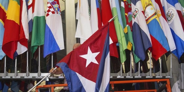 A workman at the US Department of State add the Cuban flag at to the display of flags inside the main entrance at 202 'C' Street at 4am local time (0800 GMT) in Washington, DC on July 20, 2015. The United States and Cuba formally resumed diplomatic relations on July 20, as the Cuban flag was raised at the US State Department in a historic gesture toward ending decades of hostility between the Cold War foes.      AFP PHOTO / Paul J. Richards        (Photo credit should read PAUL J. RICHARDS/AFP/G