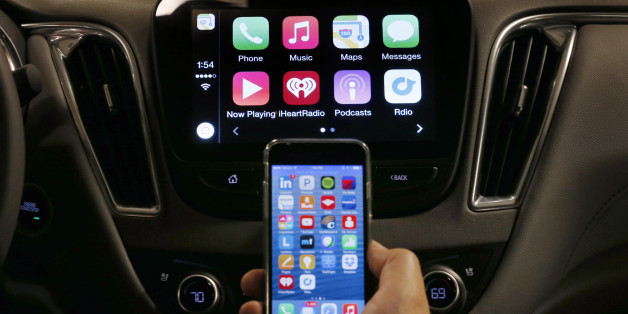 An iPhone is connected to a 2016 Chevrolet Malibu equipped with Apple CarPlay apps, displayed on the car's MyLink screen, top, during a demonstration in Detroit, Tuesday, May 26, 2015. Starting with Chevrolet this summer, many General Motors models will offer Apple's CarPlay and Google's Android Auto systems that link smart phones with in-car screens and electronics. (AP Photo/Paul Sancya)