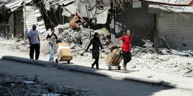 Des habitants de la ville de Damas collectent des cartons d'aide alimentaire, le 22 aout 2014