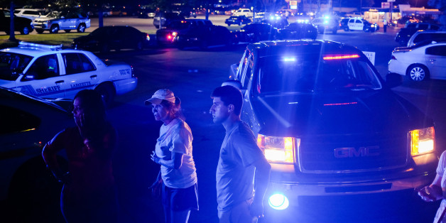 Bystanders look on as emergency personnel respond to the scene of a deadly shooting at the Grand Theatre in Lafayette, La., Thursday, July 23, 2015. (AP Photo/Denny Culbert)